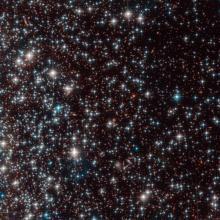 Bedin 1, visible como una colección de débiles estrellas en la parte superior izquierda de la imagen